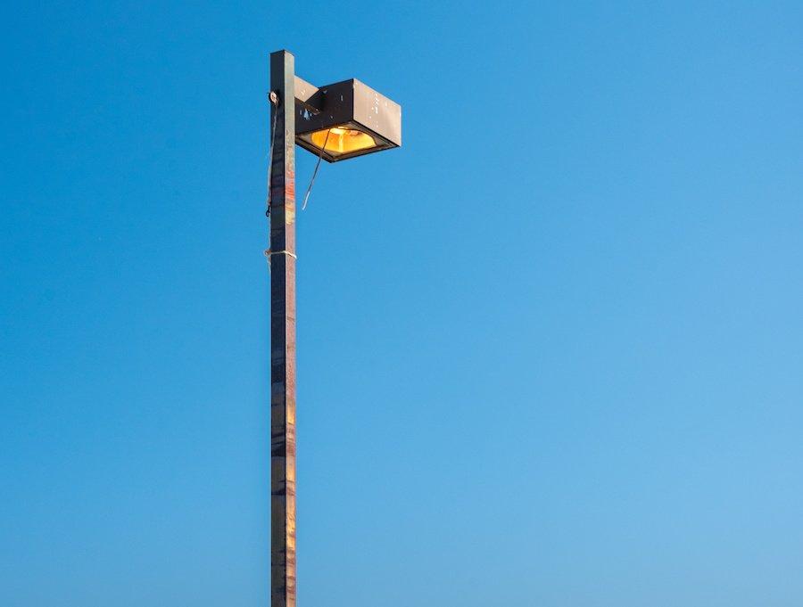 Big metal city light pole on a blue sky